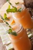 Honeydew melon juice closeup on wooden background, vertical Royalty Free Stock Photos