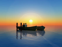 Honeymoon. Young couple fallen in love sitting in a boat expecting the sun to rise Stock Photo