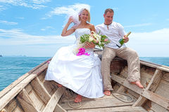 Honeymoon. Romentic trip after wedding sitting in an boat with champagne Royalty Free Stock Photos