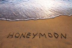 Honeymoon. Word Honeymoon written on the beach royalty free stock photography
