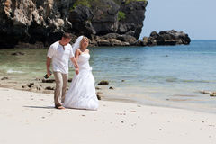 Honeymoon on the beach. Groom and bride with wedding gown Stock Photos