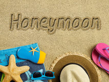 Honeymoon on the beach. Honeymoon text on sand and beach accessories Royalty Free Stock Photo