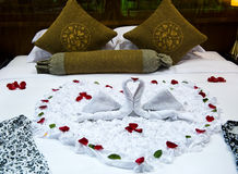 Honeymoon bed. Two swans and heart made from towels on honeymoon bed Stock Image