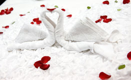 Honeymoon bed. Two swans and heart made from towels on honeymoon bed Stock Photography