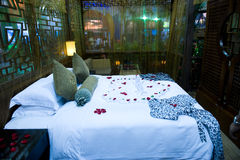 Honeymoon bed. Topped with rose petals Royalty Free Stock Photography