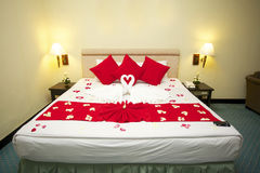 Honeymoon bed. Decorated with red rose petals and towels Royalty Free Stock Photos