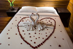 Honeymoon bed. Decorated by red rose in heart shape white sheet Royalty Free Stock Photography