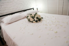 Honeymoon bed. Decorated with white rose Stock Photos