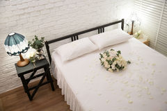 Honeymoon bed. Decorated with white rose Royalty Free Stock Images