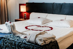 Honeymoon bed decoration. Honeymoon bed decorated with red rose petals and towels Stock Photo