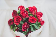 Honeymoon bed look like heart shape with rose petals for honeymo. On lover. In the white bed of the hotel for couples.Decorated with bright red roses Stock Photos