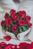 Honeymoon bed look like heart shape with rose petals for honeymo. On lover. In the white bed of the hotel for couples.Decorated with bright red roses Stock Image