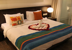 Honeymoon Bed. Two swans and heart made from towels on honeymoon bed in a Hotel room Stock Photos