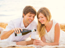 Honeymoon concept, Man and Woman in love. Couple enjoying glass of champagne on tropical beach at sunset Royalty Free Stock Photo