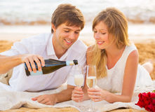 Honeymoon concept, Man and Woman in love. Couple enjoying glass of champagne on tropical beach at sunset Royalty Free Stock Photos