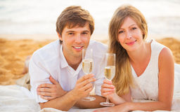 Honeymoon concept, Man and Woman in love. Couple enjoying glass of champagne on tropical beach at sunset Stock Photography