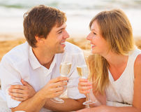 Honeymoon concept, Man and Woman in love. Couple enjoying glass of champagne on tropical beach at sunset Stock Photos