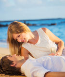Honeymoon concept, Man and Woman in love. Man and Woman in love, Couple enjoying glass of champagne on tropical beach at sunset, Honeymoon concept Stock Images