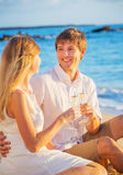 Honeymoon concept, Man and Woman in love. Man and Woman in love, Couple enjoying glass of champagne on tropical beach at sunset, Honeymoon concept Stock Image