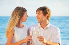 Honeymoon concept, Man and Woman in love. Man and Woman in love, Couple enjoying glass of champagne on tropical beach at sunset, Honeymoon concept Royalty Free Stock Photo