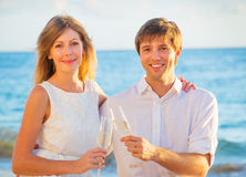 Honeymoon concept, Man and Woman in love. Man and Woman in love, Couple enjoying glass of champagne on tropical beach at sunset, Honeymoon concept Stock Photography