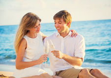 Honeymoon concept, Man and Woman in love. Man and Woman in love, Couple enjoying glass of champagne on tropical beach at sunset, Honeymoon concept Stock Photos