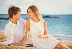 Honeymoon concept, Man and Woman in love. Man and Woman in love, Couple enjoying glass of champagne on tropical beach at sunset, Honeymoon concept Royalty Free Stock Photos