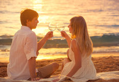 Honeymoon concept, Man and Woman in love. Couple enjoying glass of champagne on tropical beach at sunset, Beautiful sunset light Stock Photos