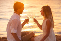 Honeymoon concept, Man and Woman in love. Couple enjoying glass of champagne on tropical beach at sunset, Beautiful sunset light Royalty Free Stock Photography