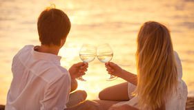 Honeymoon concept, Man and Woman in love. Couple enjoying glass of champagne on tropical beach at sunset, Beautiful sunset light Stock Photo