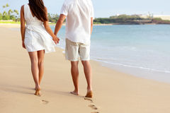 Honeymoon couple holding hands walking on beach stock photo