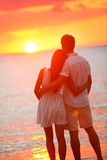 Honeymoon couple hugging in loving relationship. Honeymoon couple romantic in love at beach sunset. Newlywed happy young couple hugging enjoying ocean sunset Stock Photo