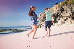 Honeymoon couple just married. Honeymoon couple jogging or running at the beach Stock Image