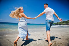 Honeymoon couple just married. Honeymoon couple jogging or running at the beach Royalty Free Stock Image