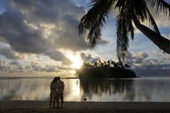 Honeymoon couple looks at the sunrise from a tropical pacific is. Land beach in Muri lagoon in Rarotonga, Cook Islands. Real people. Copy space stock images