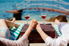 Honeymoon couple relax on beach. Holding hands together with vine background Royalty Free Stock Images