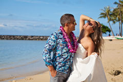 Honeymoon couple romantic in love. Couple in love hugging on a tropical Hawaiian beach with a pacific ocean in the background. Summer travel holidays vacation Stock Photography