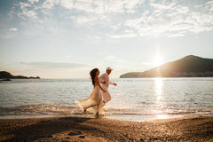 Honeymoon couple. Running on the beach with sun and blue sky Stock Image