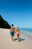 Honeymoon couple walking along the sea shore Royalty Free Stock Photos