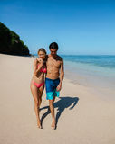 Honeymoon couple walking on the beach. Full length shot of young honeymoon couple walking on the beach. Young men and women in swimwear strolling on the sea Royalty Free Stock Photos