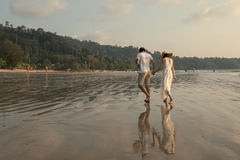 Honeymoon couples in love holding hands walking on the beach at royalty free stock photography