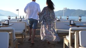 Honeymoon, happy Lovers into bathing suits walks together on pier at sea at summer holidays stock video