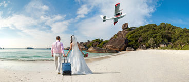 Honeymoon. Happy newly married couple in honeymoon, on sun sandy beach in Thailand stock photography