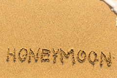 Honeymoon - inscription on sand beach. Abstract. Stock Photography