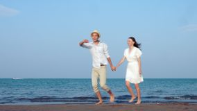 Honeymoon newlywed married young couple on beach walking in love holding hands stock video