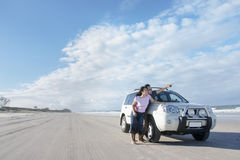 Honeymoon road trip at the beach. Young couple is enjoying her honeymoon at the beach beside a car Royalty Free Stock Photo