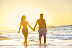 Honeymoon romantic couple in love at beach sunset. Romantic honeymoon couple in love holding hands walking on beautiful sunset at beach in waterfront. Lovers or Royalty Free Stock Images