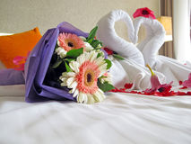Honeymoon room. Two swans made of towels and Bridal bouquets in hotel's honeymoon room Royalty Free Stock Photo