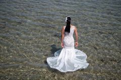 Honeymoon at sea resort. Wedding abroad. Wedding ceremony seashore. Bride white wedding dress stand in sea water. Wet. Wedding dress hot sunny day. Bride happy royalty free stock photo