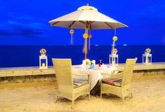 Honeymoon table set up dinner on the beach. Romantic honeymoon  table set up dinner on the beach, twilight time, blue ribbin Royalty Free Stock Photo